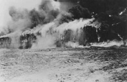 """<p>Buildings of the <a href=""""/narrative/8176/en"""">Bergen-Belsen</a> concentration camp is burned to the ground to halt the spread of typhus. Germany, May 21, 1945.</p>"""