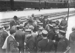 "<p>A group of Jewish men on a train platform with French policemen at the Austerlitz station before deportation to the Pithiviers internment camp. <a href=""/narrative/6033"">Paris</a>, France, May 1941.</p>"