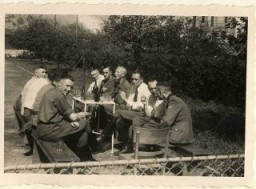 <p>Karl Höcker (on left, looking at the camera) relaxes with SS physicians, including Dr. Fritz Klein (far left), Dr. Horst Schumann (partially obscured next to Klein, identified from other photographs), and Dr. Eduard Wirths (third from right, wearing tie).</p>