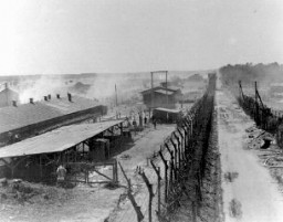"""<p>A view of the <a href=""""/narrative/4549"""">Bergen-Belsen</a> concentration camp after the <a href=""""/narrative/2317"""">liberation</a> of the camp. Bergen-Belsen, after April 15, 1945.</p> <p>As it drove into Germany, the British <a href=""""/narrative/8176"""">11th Armoured Division</a> occupied the Bergen-Belsen concentration camp on April 15, 1945.When the 11th Armoured Division entered the camp, its soldiers were totally unprepared for what they found. Inside were more than 60,000 emaciated and ill prisoners in desperate need of medical attention. More than 13,000 corpses in various stages of decomposition lay littered around the camp.</p>"""