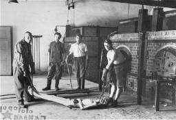 <p>Survivors of the Dachau concentration camp demonstrate the operation of the crematorium by preparing a corpse to be placed into one of the ovens. Dachau, Germany, April 29–May 10, 1945.</p>