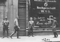 """<p>Shortly after the German annexation of <a href=""""/narrative/5815/en"""">Austria</a>, Nazi Storm Troopers stand guard outside a Jewish-owned business. Graffiti painted on the window states: """"You Jewish pig may your hands rot off!"""" <a href=""""/narrative/6000/en"""">Vienna</a>, Austria, March 1938.</p>"""