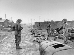 Members of the medical detachment of Combat Command A, 12th Armored Division, XXI Corps, US 7th Army, view the burned corpses of victims at Kaufering IV.