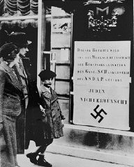 """<p>Viennese pedestrians view a large Nazi sign posted on a restaurant window informing the public that this business is run by an organization of the Nazi Party and that Jews are not welcome. Vienna, <a href=""""/narrative/5815/en"""">Austria</a>, March-April 1938.</p>"""