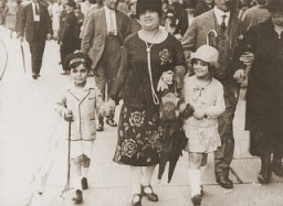 Simone Weil (right), her mother Jeanne, and her brother Roger stroll along a street in Strasbourg.