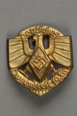 """<p>This badge shows the Hitler Youth insignia and Nazi German national symbol superimposed over ring bearing the raised text, """"Deutsches/Jugendfest 1936.""""</p> <p>Beginning in 1933, the <a href=""""/narrative/52091"""">Hitler Youth</a> and the League of German Girls had an important role to play in the new Nazi regime. Through these organizations, the Nazi regime planned to<a href=""""https://encyclopedia.ushmm.org/narrative/11357/en"""">indoctrinate young people</a> with Nazi ideology. This was part of the process of Nazifying German society. The aim of this process was to dismantle existing social structures and traditions. The Nazi youth groups were about imposing conformity. Youth throughout Germany wore the same uniforms, sang the same Nazi songs, and participated in similar activities. Badges such as this one helped foster indoctrination and uniformity.</p>"""