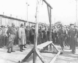 "<p>A Dutch survivor of the <a href=""/narrative/7757/en"">Ohrdruf</a> camp shows the camp's gallows, which the Germans used to execute prisoners, to US forces (including Generals Eisenhower, Bradley, and Patton). Germany, April 12, 1945.</p>"
