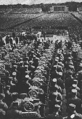 <p>Rows of SA standard bearers line the field behind the speaker's podium at the 1935 Nazi Party Congress. Adolf Hitler addresses the crowds from the podium. Nuremberg, Germany, September 1935.</p>