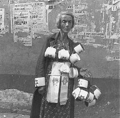 <p>An emaciated woman sells the compulsory Star of David armbands for Jews. In the background are concert posters; almost all are destroyed. Warsaw ghetto, Poland, September 19, 1941.</p>