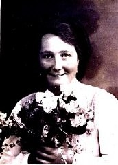 Bir buket çiçek tutan Frieda Greinegger'in fotoğrafı.