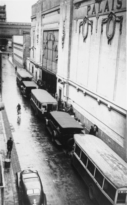 """<p>Buses waiting at the entrance to the <a href=""""/narrative/11768/en"""">Vélodrome d'Hiver</a>, where almost 13,000 Jews were assembled before being transported to Drancy and other French transit camps. Paris, France, July 16 and 17, 1942.</p>"""