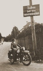"<p>A motorcyclist reads a sign stating ""Jews are not welcomed here."" Germany, ca. 1935.</p>"