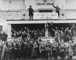 "<p>German troops marching into the Sudetenland stop at a former Czech frontier post. Nazi officials and Sudeten Germans salute the troops. The sign between the swastikas reads: ""One People, One Reich, One Führer."" Grottau, <a href=""/narrative/7295/en"">Czechoslovakia</a>, October 2 or 3, 1938.</p>"