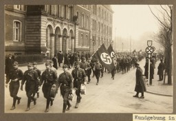 "<p>Uniformed members of the <a href=""/narrative/51797"">SA</a> parade down a city street in Duisburg during a Nazi rally, circa 1928.</p>"