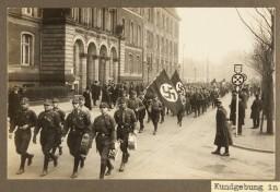 SA men parade down a city street during a Nazi rally