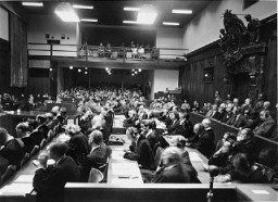 """<p>View of the courtroom as seen from the interpreters' section during the <a href=""""/narrative/9506/en"""">IG Farben Trial</a>. The defense lawyers are in the foreground, the defendants are in the dock to the right, and the spectators' gallery is on the far side of the courtroom.</p>"""