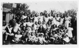 Zsofi Brunn (back row, center) poses with the orphans (previously hidden children) under her care in a JDC-sponsored orphanage outside of Budapest.