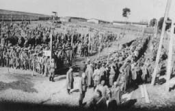 <p>Pengawal Jerman mengawasi tahanan di kamp Rovno yang diperuntukkan bagi tahanan perang Soviet. Rovno, Polandia, setelah 22 Juni 1941.</p>