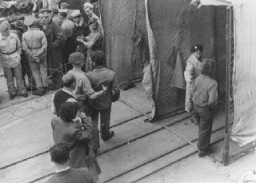 "<p>British soldiers force Jewish refugees from <a href=""/narrative/7475""><em>Aliyah Bet</em></a> (""illegal"" immigration) ship <em>Theodor Herzl</em> through a disinfection station before deporting them to <a href=""/narrative/26091"">detention camps in Cyprus</a>. Haifa port, Palestine, April 24, 1947.</p>"