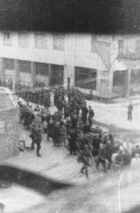 "<p>Deportation of Jews from the Warsaw ghetto during the <a href=""/narrative/3636/en"">uprising</a>. The photograph was taken from a building opposite the ghetto by a member of the resistance.  It shows Jews who were captured by the SS during the suppression of the Warsaw ghetto uprising marching past the St. Zofia hospital, through the intersection of Nowolipie and Zelasna Streets, towards the Umschlagplatz for deportation. Warsaw, Poland, April 20, 1943.</p>"
