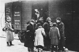 "<p>A member of the German SS supervises the boarding of Jews onto trains during a deportation action in the <a href=""/narrative/3055/en"">Krakow</a> ghetto. Krakow, Poland, 1941–1942.</p>"