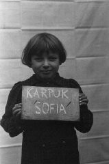 "<p class=""document-desc moreless"">Sofia Karpuk holds a name card intended to help any of her surviving family members locate her at the <a href=""/narrative/35450/en"">Kloster Indersdorf</a> displaced persons camp. This photograph was published in newspapers to facilitate reuniting the family. Kloster Indersdorf, Germany, October-November 1945. </p>