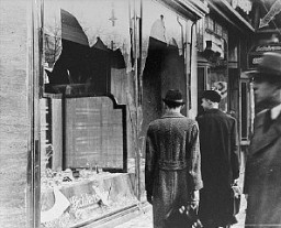 "Shattered storefront of a Jewish-owned shop destroyed during Kristallnacht (the ""Night of Broken Glass""). [LCID: 86838]"