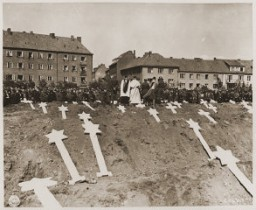 "<p>Under orders from officers of the US <a href=""/narrative/7926/en"">8th Infantry</a> Division, German civilians from Schwerin attend funeral services for 80 prisoners killed at the <a href=""/narrative/7988/en"">Wöbbeli</a>n concentration camp. The townspeople were ordered to bury the prisoners' corpses in the town square. Germany, May 8, 1945.</p>"