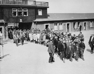 Escorted by American soldiers, child survivors of Buchenwald file out of the main gate of the camp.