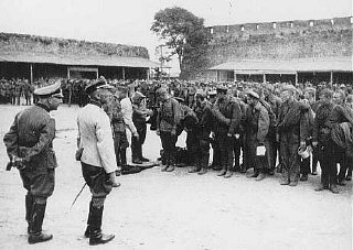 Soviet prisoners of war interrogated by German soldiers upon arrival at a prison camp.