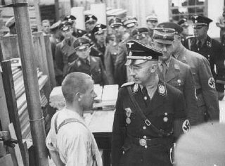 Heinrich Himmler, head of the SS, speaks to an inmate of the Dachau concentration camp during an official inspection.