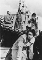 Leni Riefenstahl, with Adolf Hitler in the background, directs the shooting of a film about the Reich Party Day.