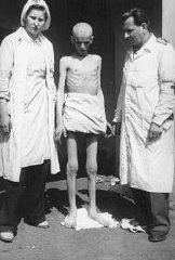 Shortly after liberation, an emaciated concentration camp inmate stands between two members of the International Red Cross.