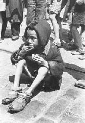 An emaciated child eats in the streets of the Warsaw ghetto.