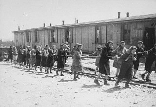 Women prisoners pull dumpcars filled with stones in the camp quarry.