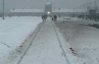 Candles mark the railway tracks leading to the Auschwitz camp