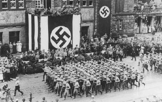 Battalions of Nazi street fighters salute Hitler during an SA parade through Dortmund.
