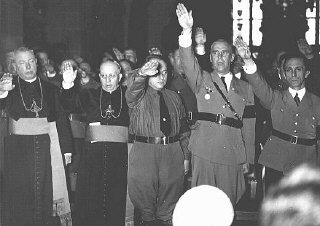 Catholic clergy and Nazi officials, including Joseph Goebbels (far right) and Wilhelm Frick (second from right), give the Nazi salute.