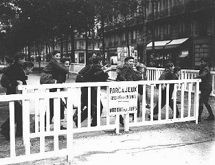 In German-occupied Paris, the fence around a children's public playground bears a sign forbidding entrance to Jews.