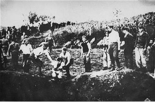 Ustasa (Croatian fascist) guards force a prisoner into a pit to be shot.