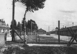 An early view of the Dachau concentration camp. Columns of prisoners are visible behind the barbed wire.