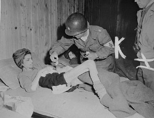 Lt. Col. J.W. Branch, Chief Surgeon of the 6th Armored Division, provides medical care to a Hungarian survivor in Penig, a subcamp ...