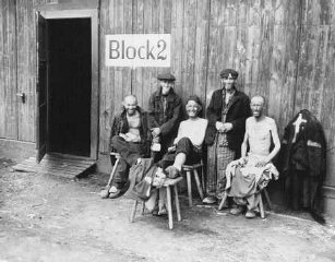Five Jewish survivors pose for a US Signal Corps photographer in front of Block 2 in the Hanover-Ahlem camp, a subcamp of Neuengamme.
