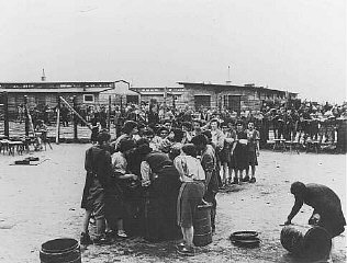 After liberation by US troops, former prisoners wait in line for soup.