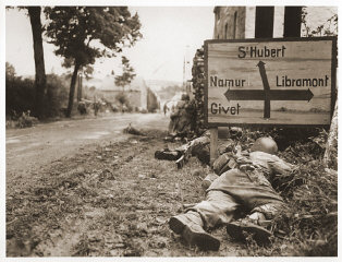 American soldiers of the 8th Infantry Regiment seek cover behind hedges and signs to return fire to German forces holding the town ...