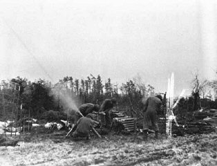 Mortar men of the 754th Tank Battalion fire an 81mm mortar at German positions during the heavy fighting in the Hürtgen Forest.
