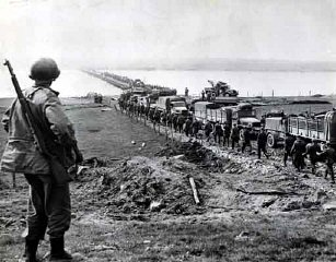 German prisoners file across the Rhine as American supply trucks move forward toward the front.